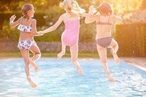 drei Mädchen springen in einen Swimming-Pool