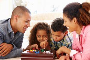 eine familie spielt gemeinsam ein brettspiel