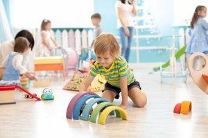 Kind spielt im Kindergarten mit Lernspielzeug