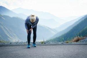frau beim joggen haelt sich den oberschenkel