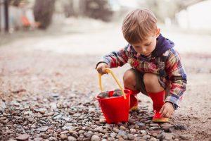 kleiner junge sammelt steine mit einem roten eimer