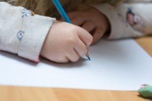 Kind hält einen Stift