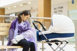 mutter bedeckt ihr kind beim stillen in einem kaufhaus mit einem schal