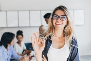 Frau lächelt, während andere Menschen im Hintergrund arbeiten