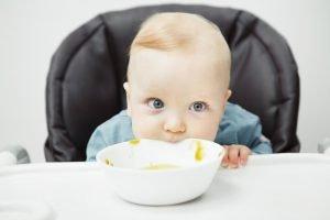 ein baby isst suppe