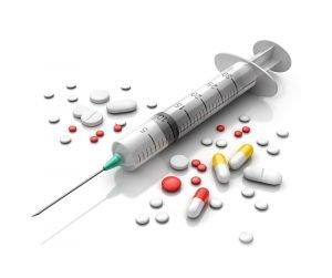 Tabletten und Spritze gegen Schuppenflechte