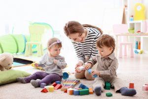 eine tagesmutter spielt mit zwei kindern