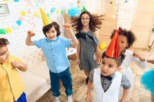 Kinder mit Partyhueten tanzen