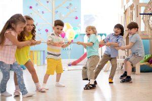 kinder spielen im kindergarten tauziehen