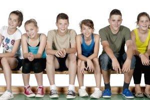 Kinder sitzen auf einer Sportbank