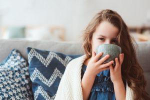 Mädchen trinkt Tee auf der Couch