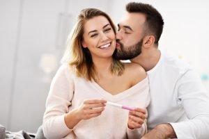 glueckliches paar mit positivem schwangerschaftstest