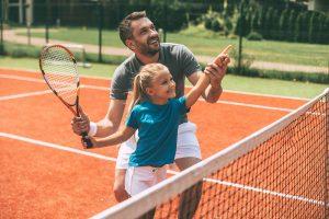 Vater und Tochter spielen Tennis