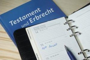 Unterlagen zum Testament und Erbrecht mit Kalender auf einem Tisch
