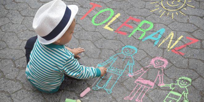 Kind malt mit Kreide Wort Toleranz