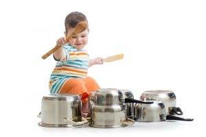 ein junge spielt auf toepfen schlagzeug