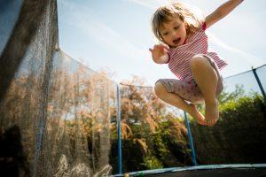 Kind springt auf einem Trampolin