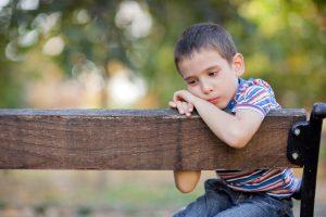 trauriges kind sitzt auf einer bank.