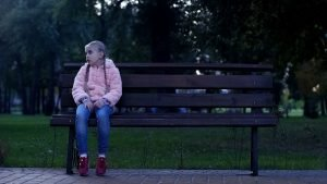 trauriges Kind sitzt allein auf einer Bank