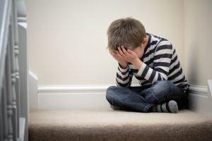 trauriges Kind sitzt auf dem Boden