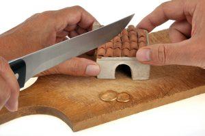 Haus wird mit einem Messer zerschnitten