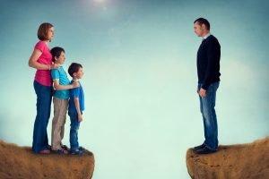 Mutter steht mit Kinder auf einer Seite, der Vater auf der anderen Seite eines Grabens