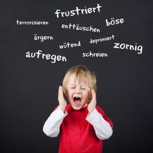schreiendes Kind vor einer Tafel mit negativ besetzten Begriffen