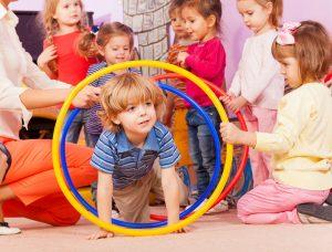 Kind krabbelt in der Gruppe durch einen Reifen