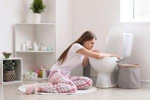schwangere frau mit uebelkeit neben der toilette