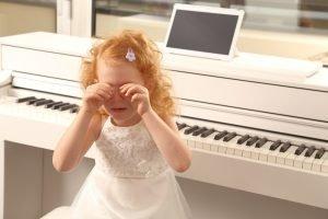 Mädchen weint am Klavier