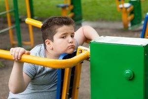 uebergewichtiges kind sitzt auf einem spielplatz herum
