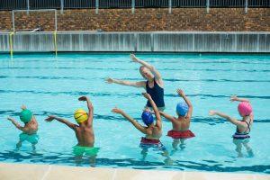 eine lehrerin macht mit kindern uebungen im schwimmunterricht