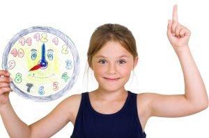Mädchen hält selbstgebastelte Uhr in der Hand