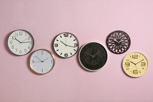 verschiedene Uhren vor einem rosafarbenen Hintergrund