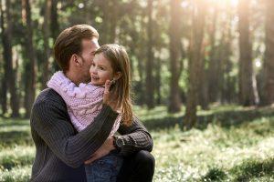 Vater umarmt seine Tochter im Wald