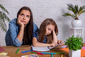Eine ungeduldige Mutter wartet darauf dass ihr Kind die Hausaufgaben beendet.