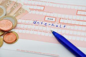 Überweisungsträger mit der Aufschrift Unterhalt sowie Bargeld