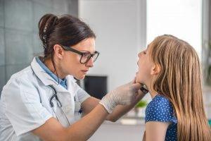 Untersuchung der Mandeln von einer Ärztin
