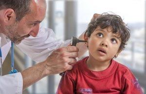 Arzt untersucht die Ohren eines kleinen Jungen auf eine Sprachentwicklungsverzögerung