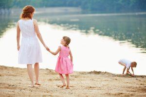 Mutter mit zwei Kindern am Strand