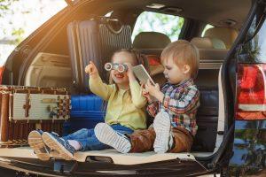 Kinder spielen im Kofferraum eines PKWs