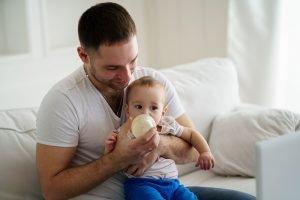ein junger vater gibt seinem kind die flasche