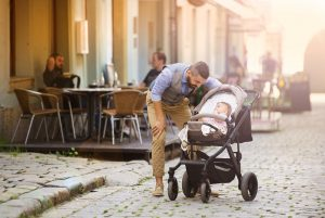 Vater schaut nach seinem Kind im Kinderwagen