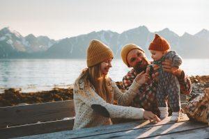ein junges paar sitzt mit ihrem baby an einem see mit bergen im hintergrund