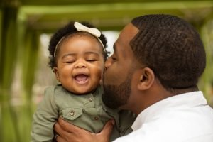 Vater küsst Tochter auf Wange