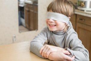 Kind laechelt mit verbundenen Augen