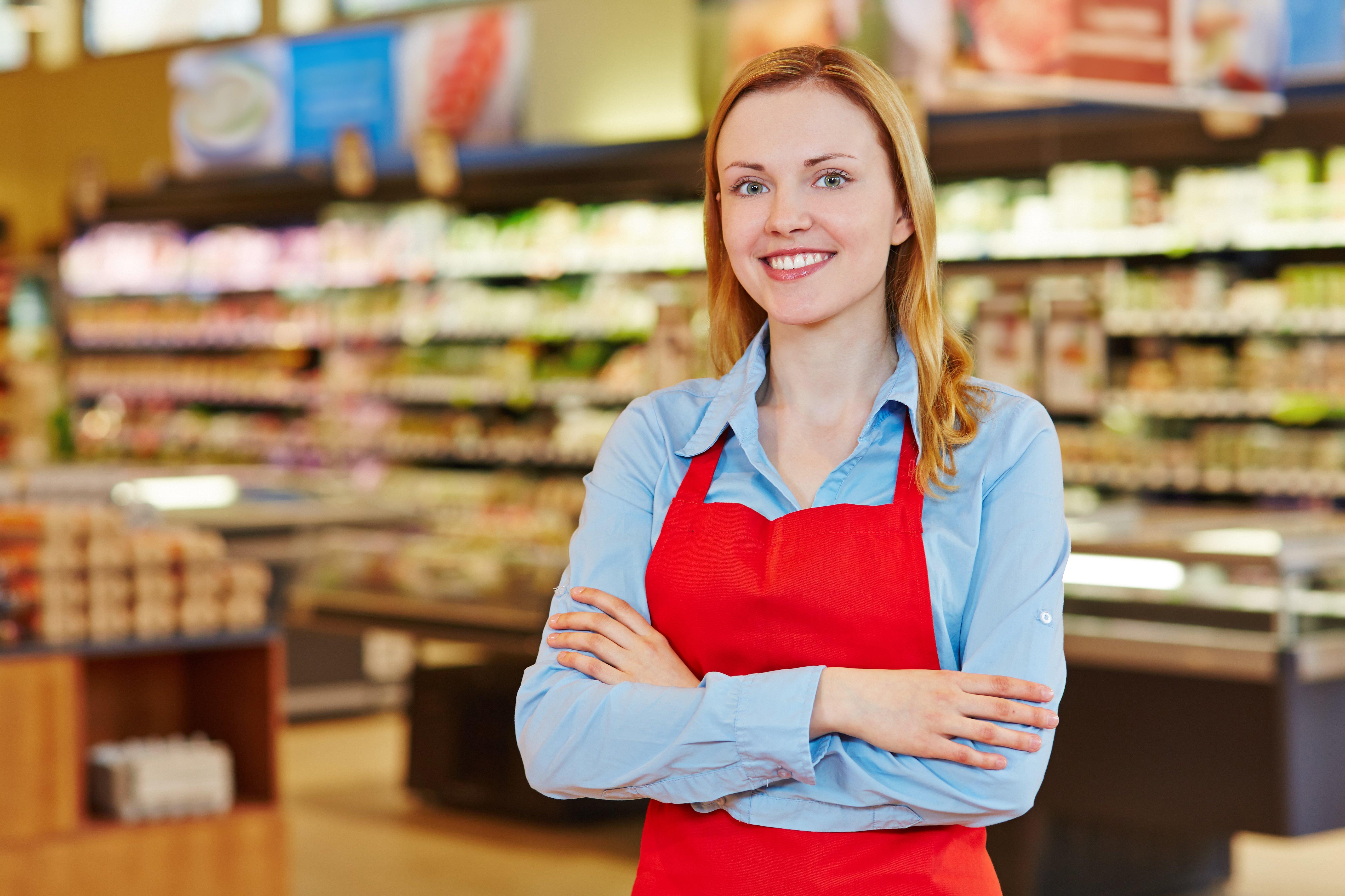 Junge Verkäuferin mit Schürze steht lächelnd im Supermarkt