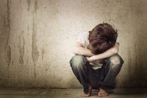 ein vernachlässigtes Kind sitzt auf dem Boden