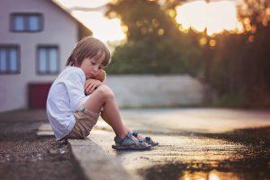 Kind sitzt allein an der Straße