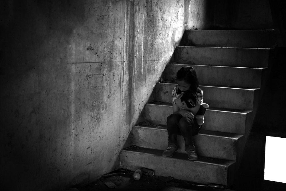 Kind sitzt traurig auf treppe